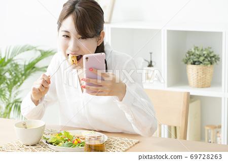 식사를하면서 스마트 폰을 보는 여자 69728263