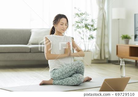집에서 요가를하는 젊은 여성 컴퓨터 69729510