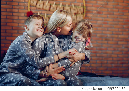 Family sitting on a bed 69735172