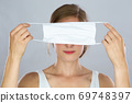 Blond woman holding face mask covering her eyes in front of her head 69748397