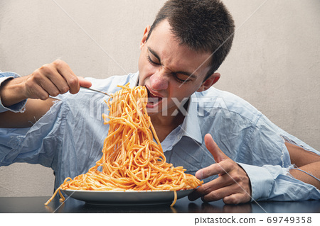 man eating spaghetti with tomato sauce 69749358