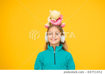 A toy bear hug for you. Happy small child hold soft toy on head 69751452