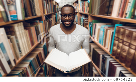 Ethnic African American guy reading book. 69754225