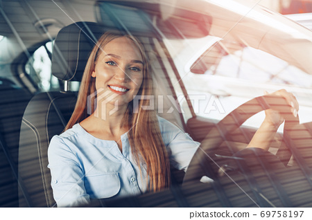 Attractive young woman sitting in new car in showroom 69758197