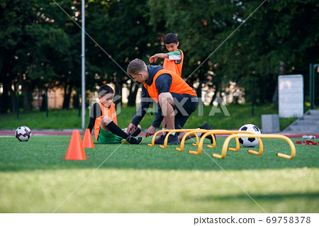 Teen soccer player injured his leg during training. Kids injury in sport concept. Coach help his pupil after accident. 69758378
