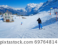 Skier skiing downhill in high mountains Kleine Scheidegg station at Switzerland 69764814