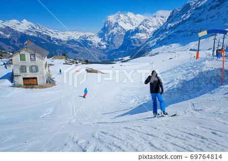 Skier skiing downhill in high mountains Kleine Scheidegg station at Switzerland 69764814