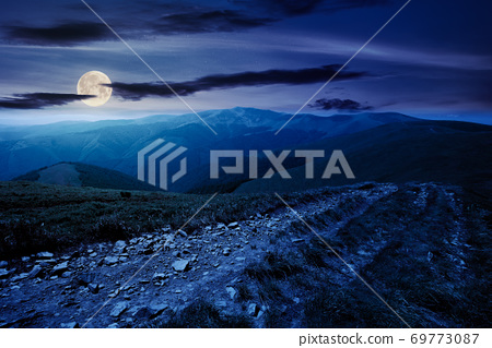 mountain road through grassy meadow at night. wonderful summer adventure in full moon light. clouds on the blue sky 69773087