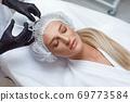 Woman getting cosmetic injection of botox in cheek, closeup. 69773584