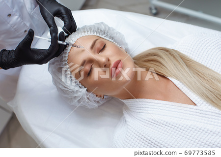 Woman getting cosmetic injection of botox in cheek, closeup. 69773585