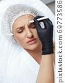 Woman getting cosmetic injection of botox in cheek, closeup. 69773586