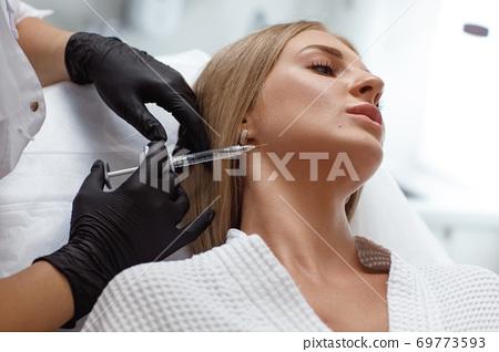 Biorevitalization procedure. Beautician making injection in woman's face 69773593