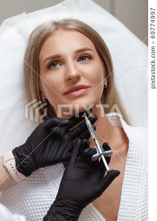 Biorevitalization procedure. Beautician making injection in woman's face 69774997