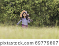 A cute, long-haired Asian schoolgirl walking holding her guitar in a meadow. 69779607
