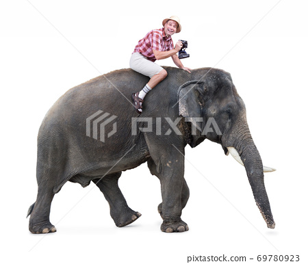 tourist rides on an elephant and carrying a camera 69780923
