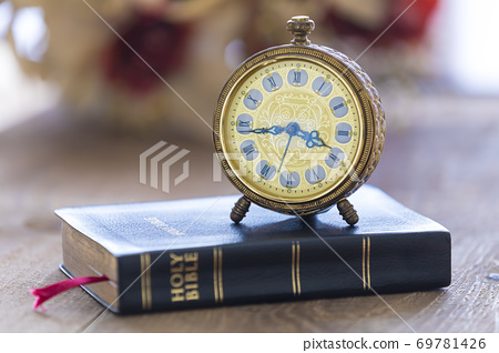 Old alarm clock on Holy bible with flowers on wooden table 69781426