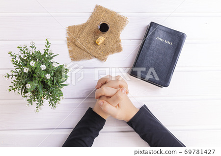 Young woman praying and Taking communion  - the wine and the bread symbols of Jesus Christ blood and body with Holy Bible 69781427