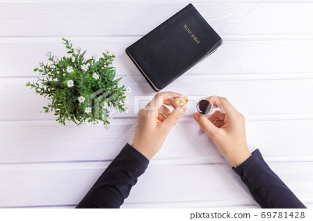 Young woman praying and Taking communion  - the wine and the bread symbols of Jesus Christ blood and body with Holy Bible 69781428