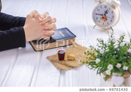 Young woman praying and Taking communion  - the wine and the bread symbols of Jesus Christ blood and body with Holy Bible 69781430