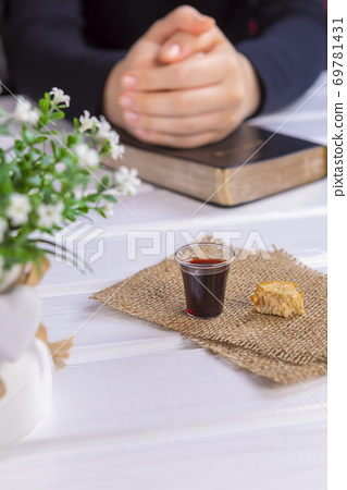 Young woman praying and Taking communion  - the wine and the bread symbols of Jesus Christ blood and body with Holy Bible 69781431