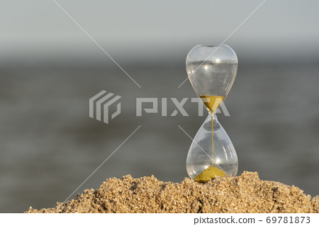 Hourglass on beach on sea background. Time concept 69781873