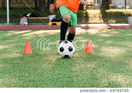 Persistent teen soccer player kicking ball on field. Close up feet of footballer kicking ball on green grass. 69789780