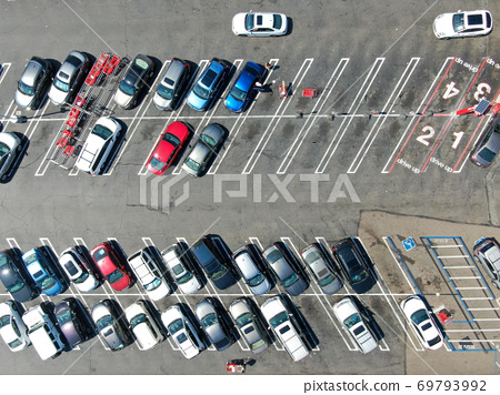 Aerial top view of parking lot at shopping mall with varieties of colored vehicles. 69793992
