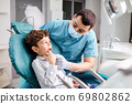 Dentist checks the child's teeth 69802862
