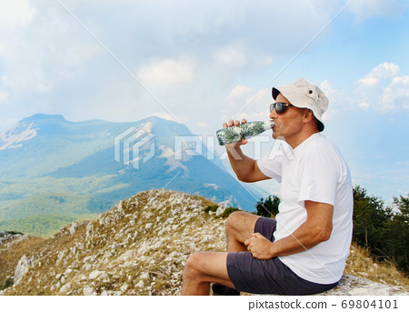 Men drinking from a reusable bottle during hiking in mountains 69804101