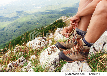 Hiker woman tying shoelaces of trekking boots close up 69804105