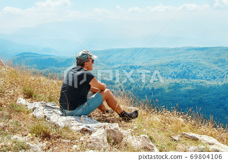 Man tourist relaxing on the top of a hill, watching wonderful scenery of mountains 69804106