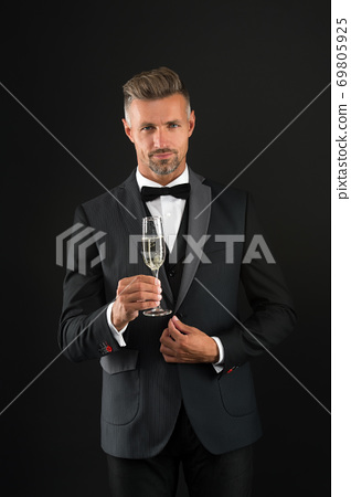 Handsome man tuxedo suit drink champagne black background, celebrate anniversary concept 69805925
