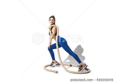 Beautiful young female athlete practicing on white studio background with shadows 69809849