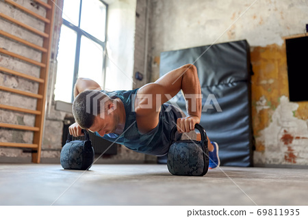 young man doing kettlebell push-ups in gym 69811935