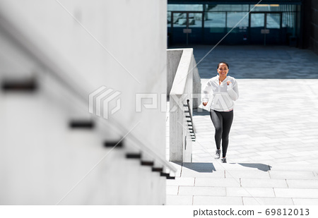 african american woman running upstairs outdoors 69812013
