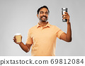 man comparing thermo cup or tumbler and coffee cup 69812084