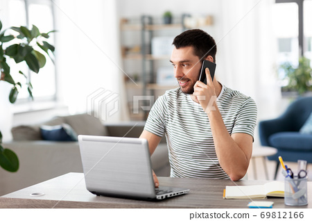 man with laptop calling on phone at home office 69812166
