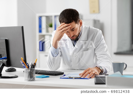 stressed male doctor with clipboard at hospital 69812438