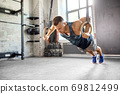 man doing push-ups on gymnastic rings in gym 69812499