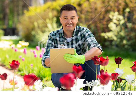 man with clipboard and flowers at summer garden 69812548