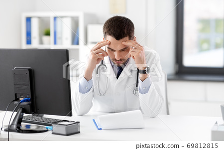 stressed male doctor with clipboard at hospital 69812815