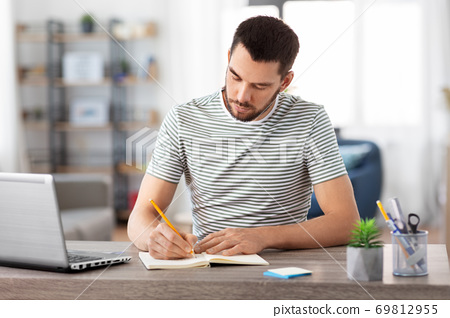 man with notebook and laptop at home office 69812955
