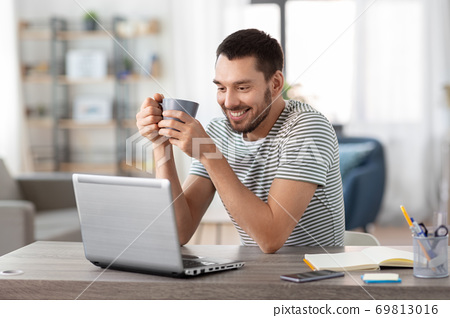 man with laptop drinking coffee at home office 69813016