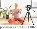 woman with camera streaming for yoga blog at home 69813065