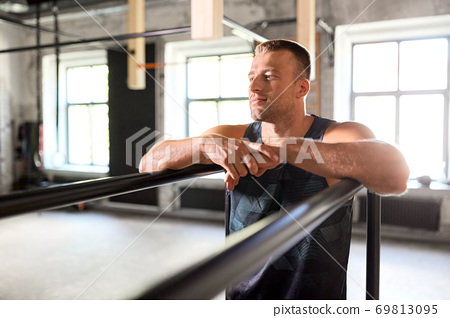 young man at parallel bars in gym 69813095