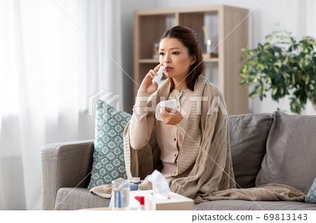 sick asian woman with nasal spray medicine at home 69813143