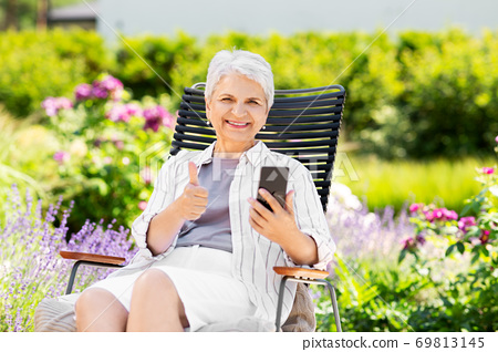 happy senior woman with phone at summer garden 69813145
