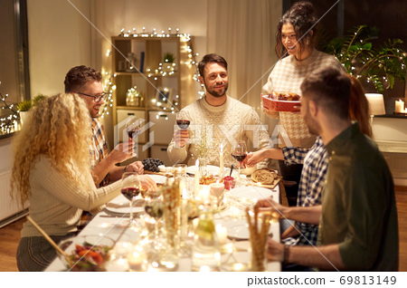 happy friends having christmas dinner at home 69813149