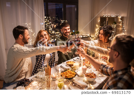 happy friends drinking red wine at christmas party 69813170