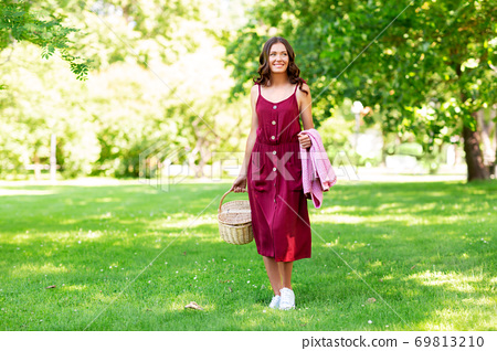 happy woman with picnic basket and blanket at park 69813210